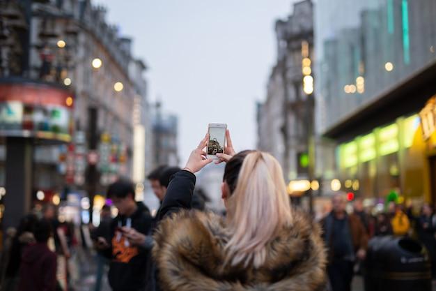 Turista della donna che prende le immagini della città con il suo telefono cellulare sulla via