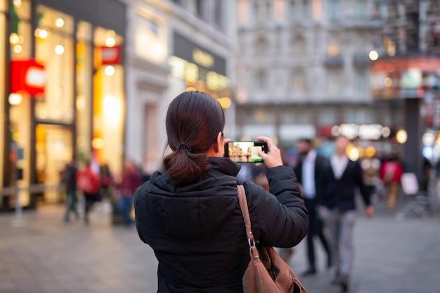 Turista della donna che prende le immagini della città con il suo cellulare