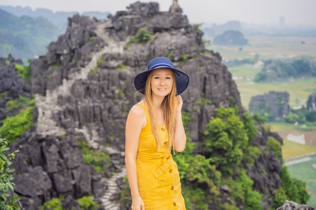 Turista sulla pagoda superiore del tempio di hang mua, risaie, ninh binh, vietnam Foto Premium
