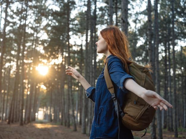 Turista della donna con uno zaino in una pineta e il tramonto sullo sfondo