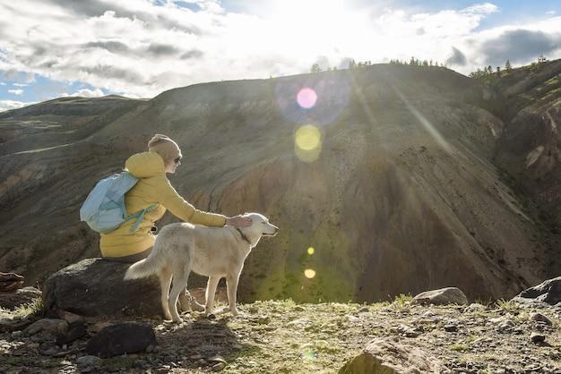 Turista con uno zaino si siede e accarezza il suo cane in montagna al tramonto. concetto di viaggio e avventura.