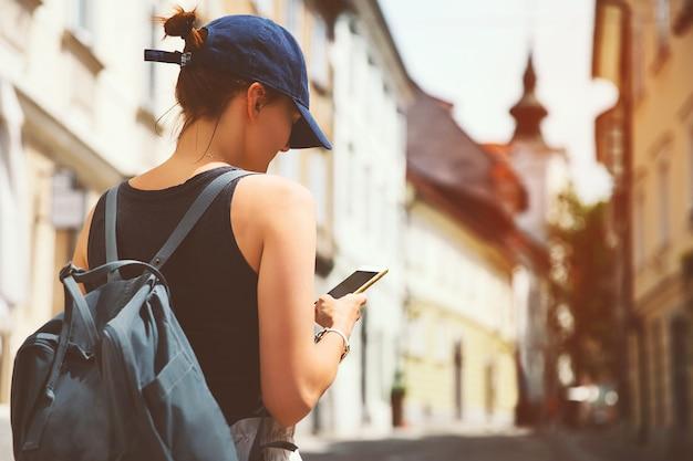 Turista con tazza di caffè utilizzando smart phone sulla strada medievale nella città vecchia di lubiana