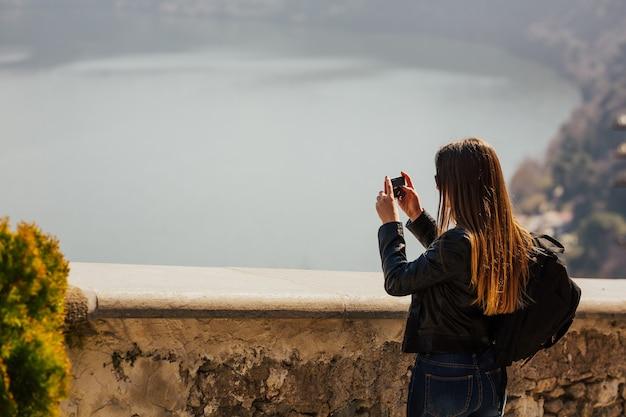 Turista della donna con capelli lunghi che cattura foto tramite smartphone sulla cima della montagna di viaggiare in italia.