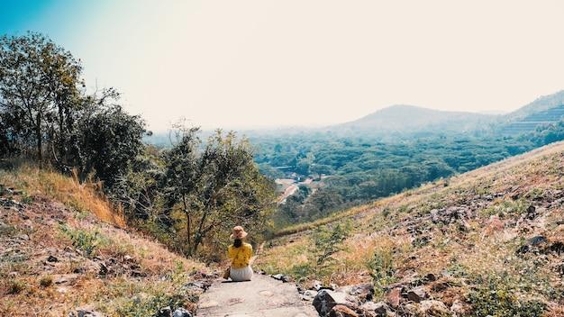 Turisti della donna che si siedono e che guardano la bellezza della vista della natura.