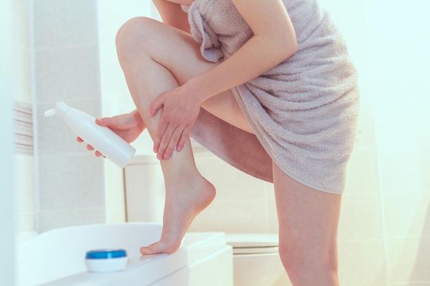 Donna in un asciugamano applicando una lozione idratante e nutriente per la pelle secca dopo aver rasato le gambe in bagno. pelle liscia, trattamenti cosmetici e igienici a casa