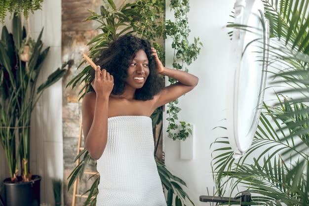 Donna in asciugamano che pettina i capelli vicino allo specchio