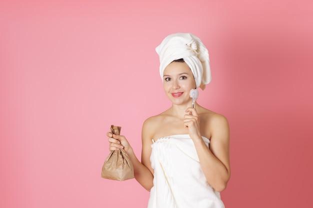 Donna in asciugamano holding scrub in sacchetto di carta e processo di pulizia della spazzola per il viso di vetro