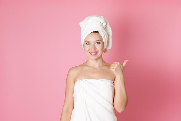 Donna in asciugamano puntare il dito nello spazio libero per il testo