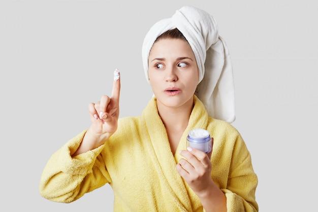 Donna in asciugamano e morbido accappatoio pubblicizza una nuova crema per il viso che aiuta a rimuovere le rughe sotto gli occhi, mostra il suo effetto sul suo esempio, isolato su un muro bianco. concetto di igiene