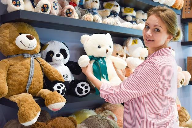 Donna nel negozio di giocattoli. selezione di orsi ripieni su uno scaffale. un visitatore nel salone dei giocattoli per bambini