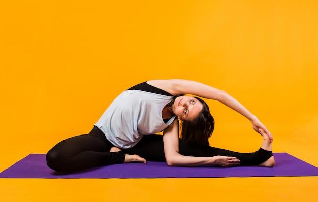 Una donna in tuta esegue lo stretching su un tappetino viola su una parete arancione
