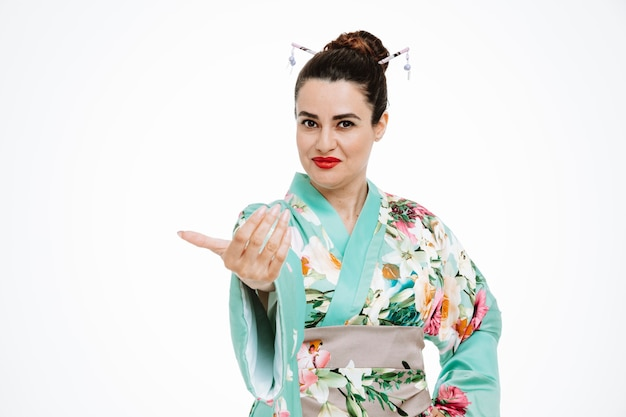 Donna in kimono tradizionale giapponese felice e positiva che viene qui gesto con la mano su bianco