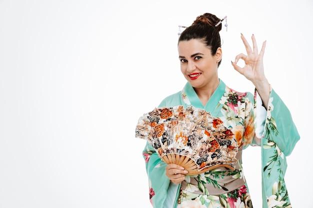 Donna in kimono tradizionale giapponese che tiene un ventaglio felice e positivo che mostra segno ok su bianco