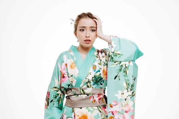 Donna in kimono tradizionale giapponese che sembra confusa e delusa tenendo la mano sulla testa per errore su bianco