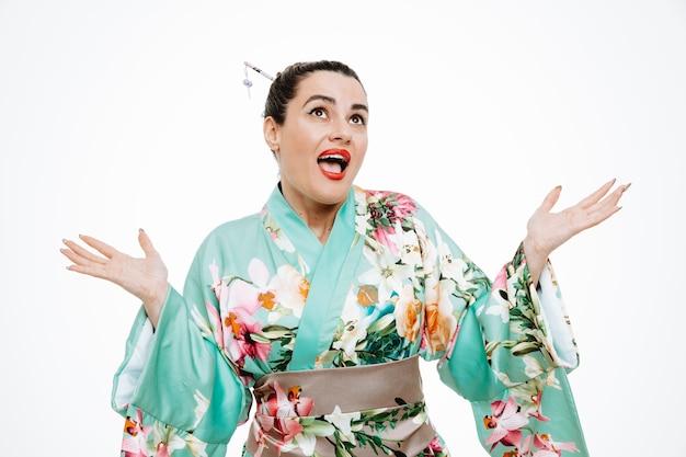 Donna in kimono tradizionale giapponese che guarda confusamente le braccia allargate ai lati senza risposta su bianco