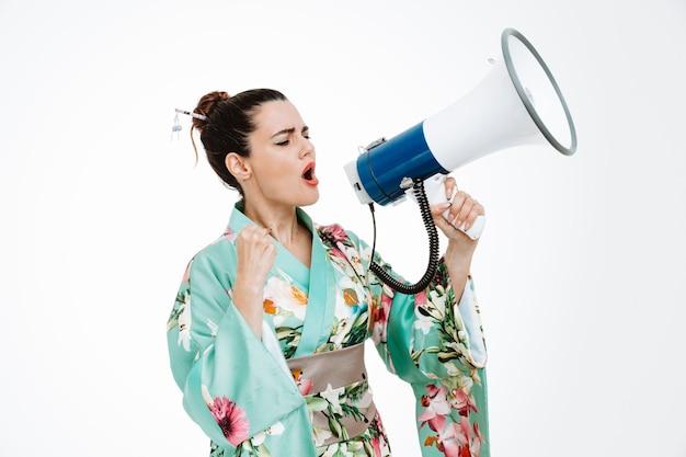 Donna in kimono giapponese tradizionale che grida al megafono che stringe il pugno essendo eccitata su bianco
