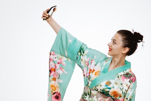 Donna in kimono giapponese tradizionale che prende selfie facendo uso dello smartphone felice e sorridente positivo sul bianco