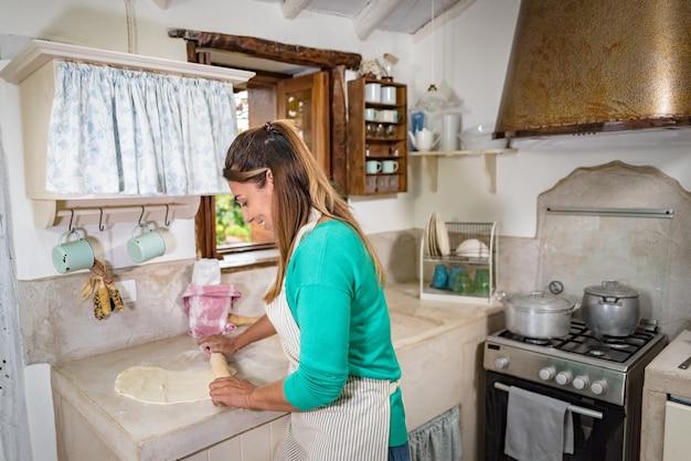 La donna in una tradizionale cucina vintage facendo un impasto per fare un pane fatto in casa