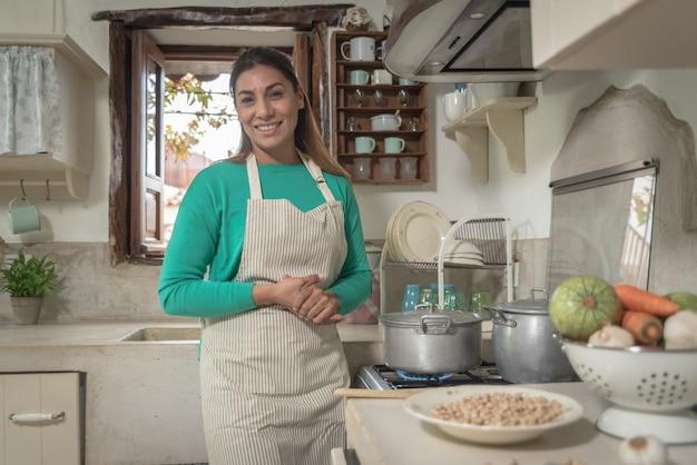 La donna in una cucina tradizionale vintage facendo un pasto con vecchie pentole e verdure