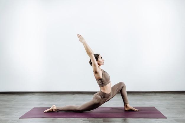 Addestratore della donna che fa yoga sul tappeto che fa posa di guerra
