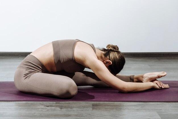 Addestratore della donna che fa yoga sul tappeto che si appoggia a una gamba dritta