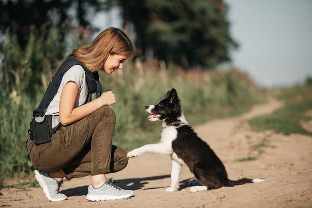 Cucciolo di cane border collie bianco e nero di addestramento della donna
