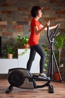 Donna che si allena a casa usando l'ellittica