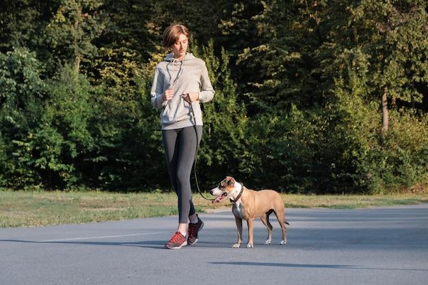 La donna addestra il suo cane a correre durante il jogging. i giovani in forma femmina e staffordshire terrier cane in una passeggiata mattutina facendo esercizio fisico