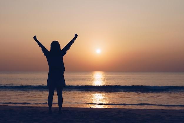 La donna viaggia in tutto il mondo con la libertà della spiaggia al tramonto estivo e il concetto di vita rilassante.