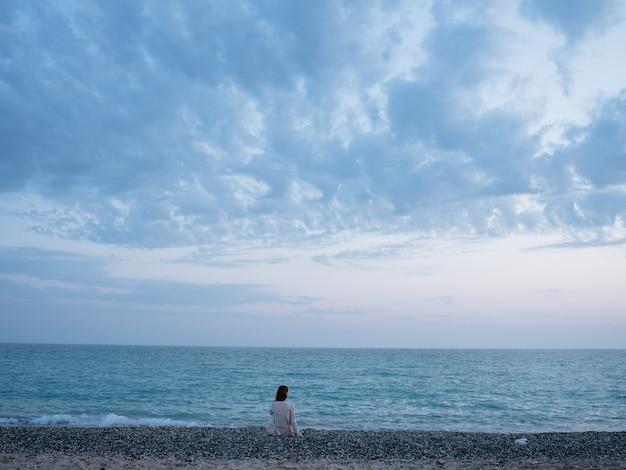 Viaggiatore della donna dall'oceano sulla spiaggia e il mare nelle nuvole di sfondo. foto di alta qualità