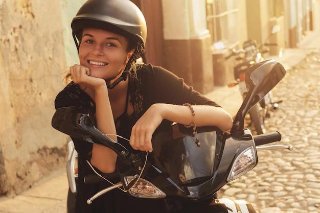 Viaggiatore della donna alla guida di scooter per le strade della città vecchia