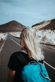 Viaggiatore donna va su desolata strada diritta su un paesaggio surreale con maestoso vulcano in lontananza. sao vicente capo verde.