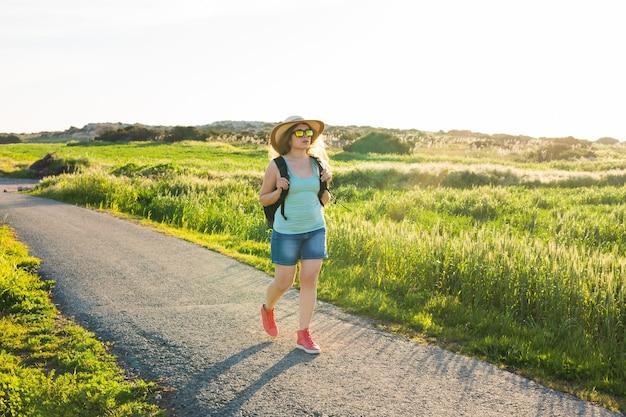 Viaggiatore della donna che guarda il tramonto al campo verde