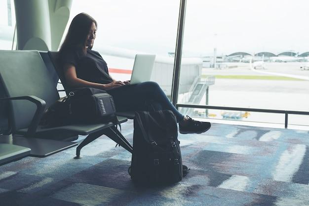 Una donna in viaggio che utilizza un computer portatile mentre è seduta in aeroporto