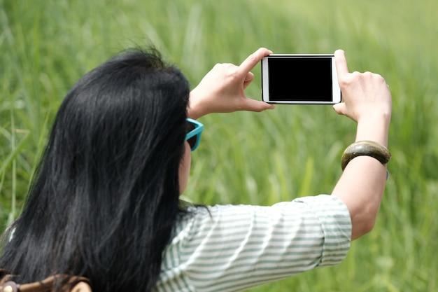 Viaggiatore della donna che per mezzo dello smart phone per sparare concetto di fondo, di viaggio e di stile di vita di vista di paesaggio del verde
