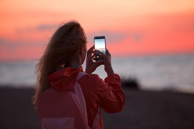 Viaggiatore della donna che utilizza smartphone e che prende foto del tramonto variopinto del mare.
