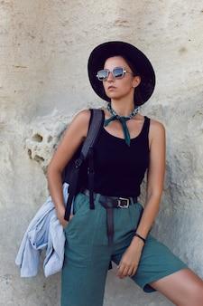 Viaggiatore donna con uno zaino e un cappello si trova accanto a una grotta nella roccia in crimea in estate