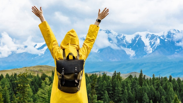 Viaggiatore della donna con uno zaino guarda la montagna con le mani alzate. viaggio e concetto di vita attiva. avventura e viaggi in montagna