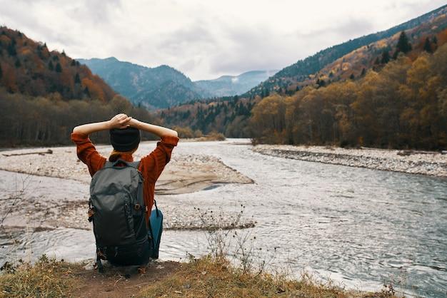 Viaggiatore della donna con uno zaino vicino al fiume sull'erba e sulle montagne nella distanza