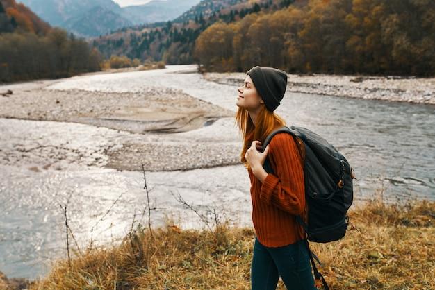 Viaggiatore della donna con lo zaino sulla sponda del fiume nella vista laterale delle montagne