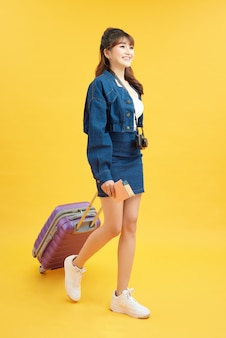 Viaggiatore donna con valigia su sfondo colorato