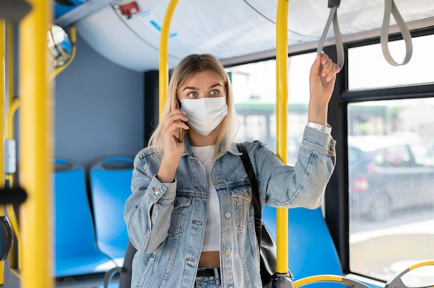Donna che viaggia in autobus pubblico parla al telefono mentre indossa una maschera medica per protezione