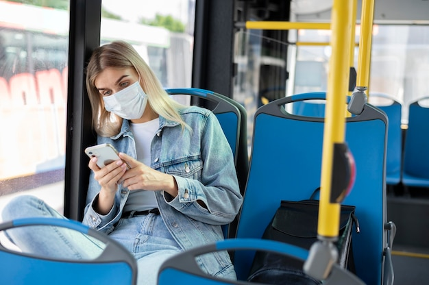Donna che viaggia in autobus pubblico utilizzando lo smartphone mentre indossa una maschera medica per protezione