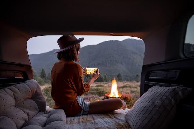 La donna viaggia in macchina in montagna