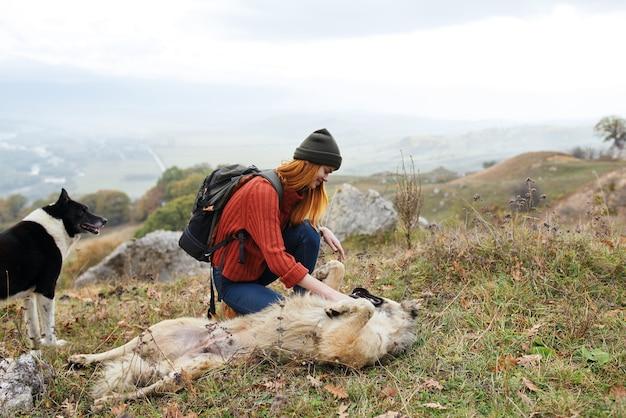 La donna viaggia in montagna con l'amicizia di un cane