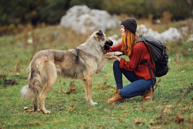 La donna viaggia nella natura con uno zaino e un cane