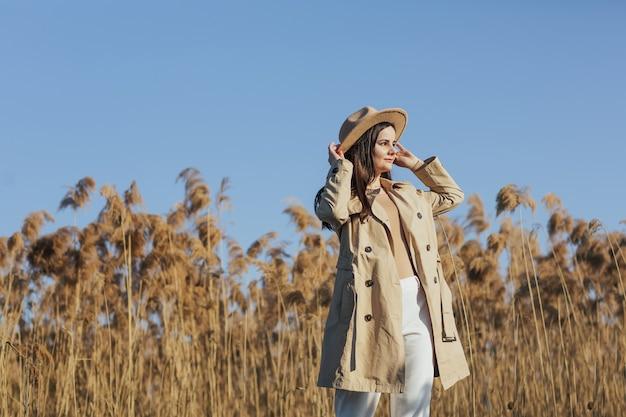 Donna in abiti alla moda in posa vicino alle canne