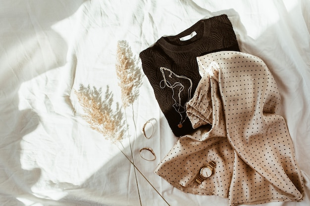 Vestiti di moda alla moda donna sul letto di lino bianco. vista piana laico e dall'alto. maglione nero, gonna di seta a pois, collana d'oro, orologio, orecchini, canne
