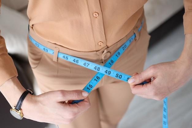 Donna in pantaloni che misurano la vita con il primo piano del nastro di centimetro