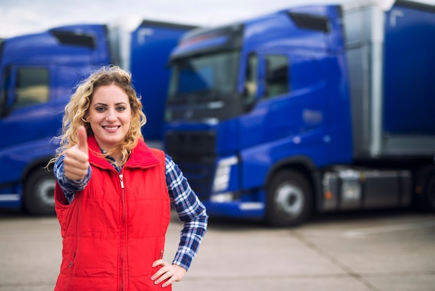 Autista di camion della donna in abbigliamento casual che tiene i pollici in su davanti ai veicoli del camion.